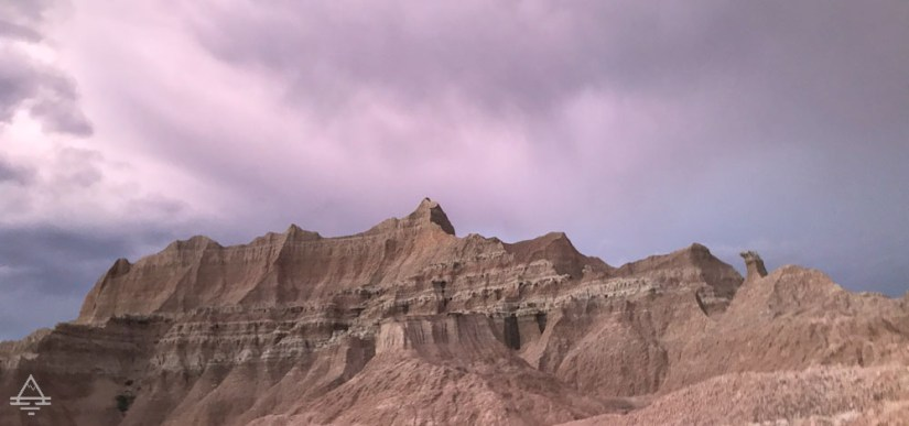 Badlands rock formation with a purple  cloudy sky