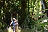 family on suspension bridge with waterfall, Rainmaker