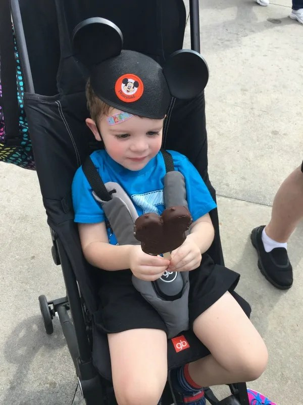 Toddler Eating Mickey Ice Cream in Stroller at Disney World
