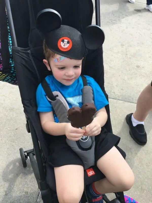 Toddler Eating Mickey Ice Cream in Stroller at Disney World