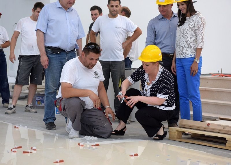 Kolinda Grabar Kitarović lijepi pločice na podu crkve Gospe Velikog Hrvatskog Krsnog Zavjeta (Foto: Ured predsjednice RH)