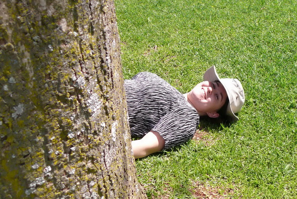 photograph of Trisha Cornelius (me) lying flat on my back after taking a photograph of the first tree on the Tree Route in the Pretoria National Botanical Garden