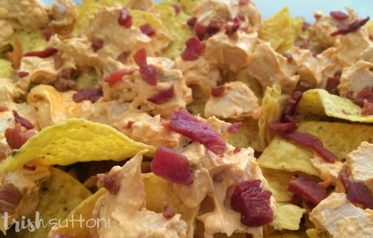 tortilla chips covered with buffalo chicken mixture and bacon pieces