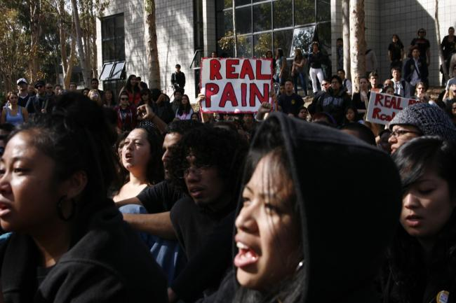 """Students protest on library walk, holding up """"Real Pain"""" and """"Real Action"""" signs. Photo courtesy of John Im & MG Abugan. 2010."""