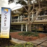 Banner displaying UC San Diego CAPS in front of their building at Galbraith Hall.