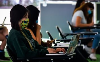 Picture of a student at a laptop with a face mask.