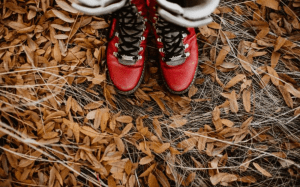 Red boots on fall leaves