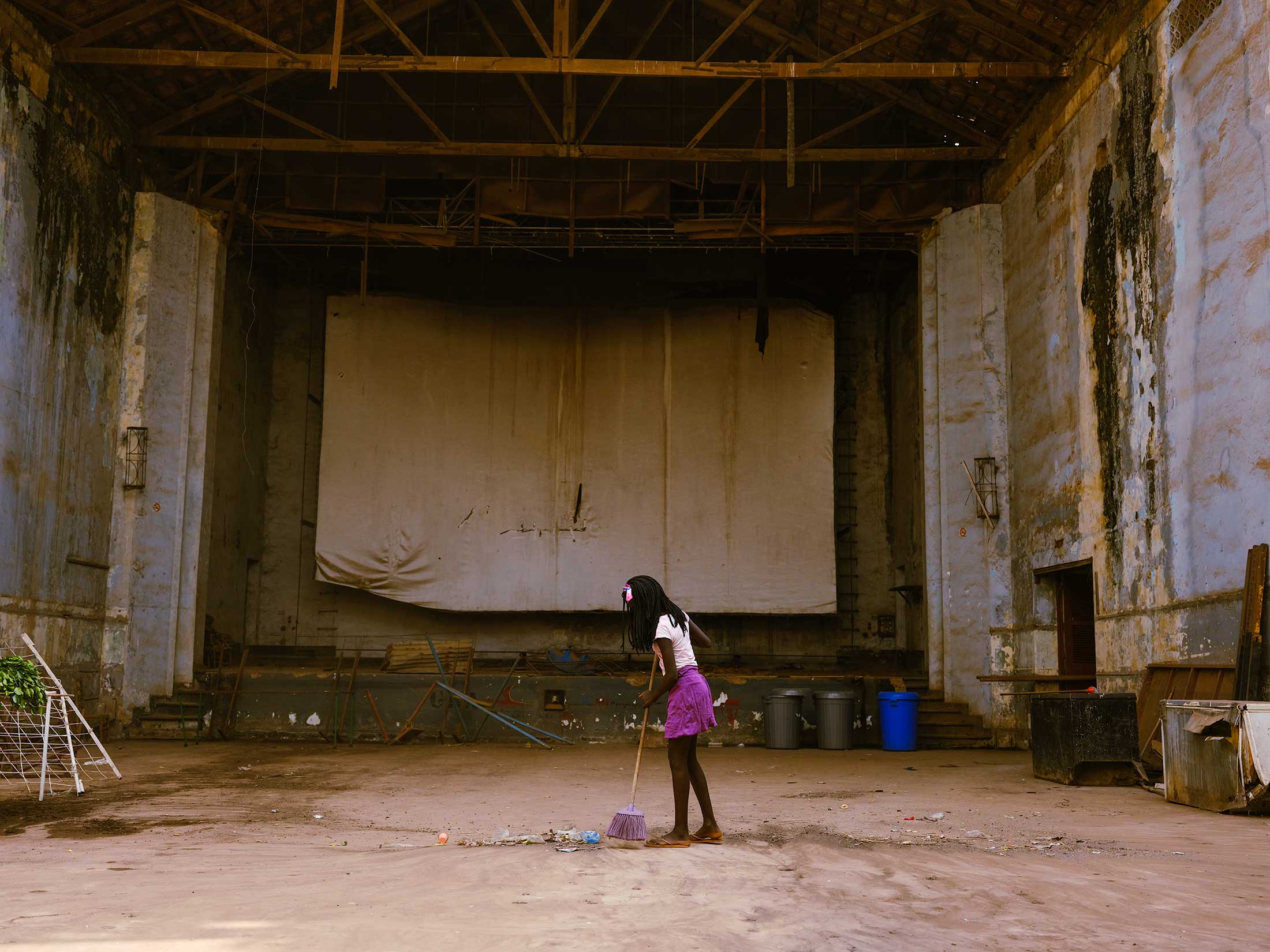 """A young girl sweeps the abandoned theater in downton Bissau. """"Women are the first to get up in the morning, and the last to go to bed at night"""" is a phrase you hear female activists in the country say often as they fight for more representation at high levels of government."""