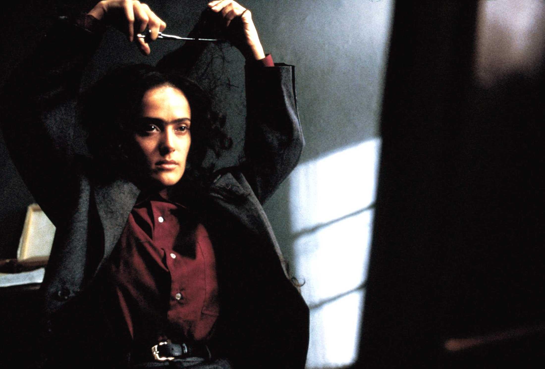Frida, Miramax / Courtesy Everett Collection. <br/> Between swigs of liquor, Frida Kahlo (Salma Hayek) impulsively cuts her hair in the 2002 eponymous film, Frida.