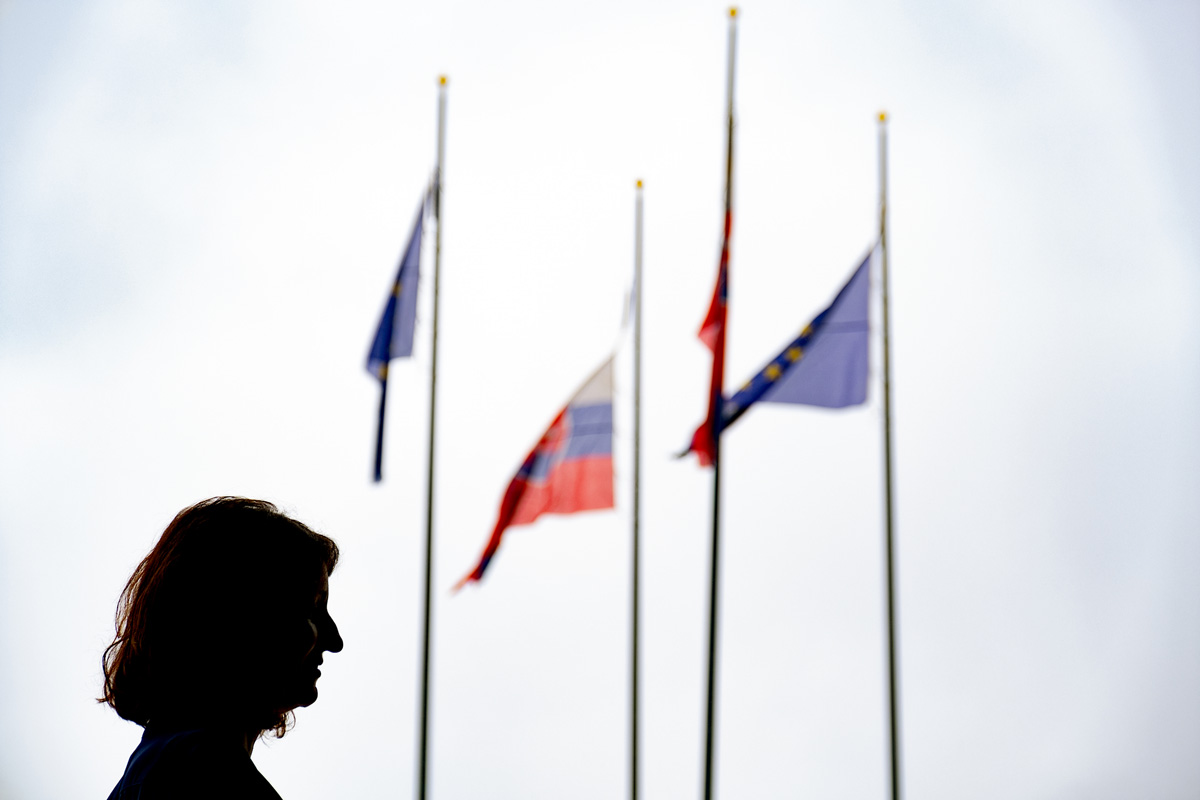 Jana Žitňanská, Vice-Chairwoman of the For the People Party, a Member of the Slovak Parliament, and Chairwoman of the Committee for Social Welfare, stands near the National Council of the Slovak Republic, or parliament building, as Slovak and European Union flags fly nearby. Žitňanská believes the coronavirus pandemic is forcing a reassessment of work/family balance in Slovakia.
