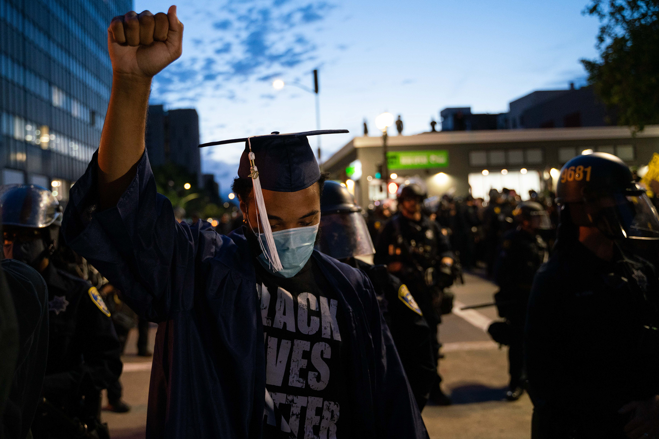 Vallejo resident Louis Michael, 22, raises his fist in solidarity after the death of George Floyd. Michael wears his graduation cap and gown during a protest on Friday, May 29 in Oakland, CA after receiving his bachelor's degree in communications from MidAmerica Nazarene University. PHOTO: SARAHBETH MANEY
