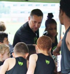 Coach Shawn in a team huddle with TTC athletes