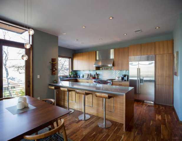 Khu vực nhà bếp trở thành một không gian đáng yêu để chuẩn bị đồ ăn. Sự kết hợp giữa gỗ và thép bạc màu cùng với đèn treo làm cho căn phòng trở nên bóng loáng.