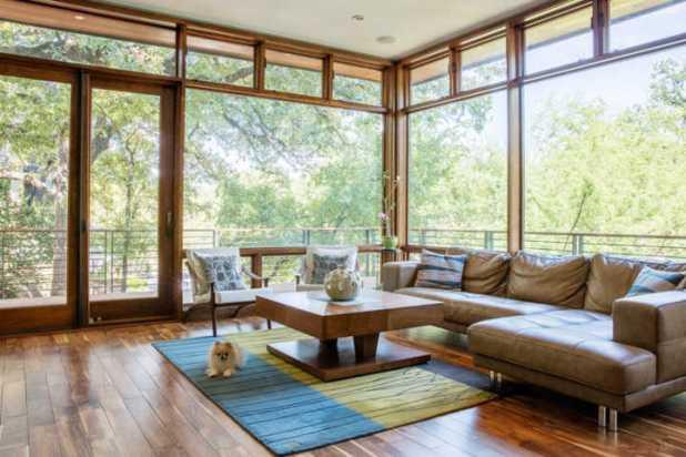 Sàn nhà cũng được đổi thành sàn gỗ mang lại sự ấm cúng cho toàn bộ ngôi nhà. Một bàn cà phê làm bằng gỗ hình chữ L, ghế da cũng được trang bị làm cho không gian sống thêm hiện đại.