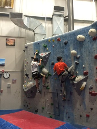 Two Scouts Climbing on the Bouldering Wall