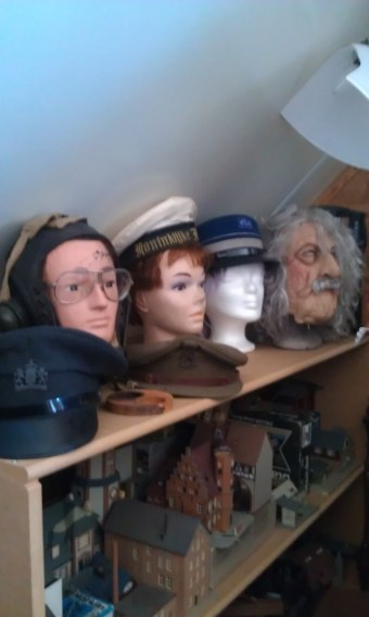 Foto. Een kast met bovenop hoeden en andere accessoires, met in de kast modelbouwwerken.