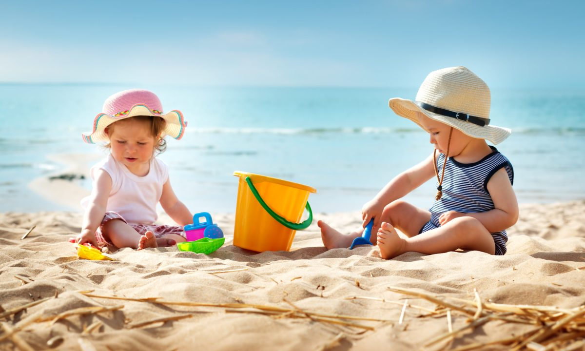 Babygirl and babyboy sitting on the beach
