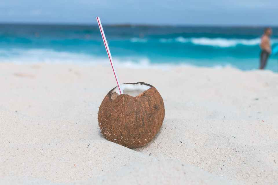 SANDY BEACH WITH OCEAN SURF IN BACKGROUND, WITH A SURFER STANIND AT THE WATER LINE. COCONUT WITH TOP CUT OFF SITTING IN SAND WITH A STRAW IN IT.