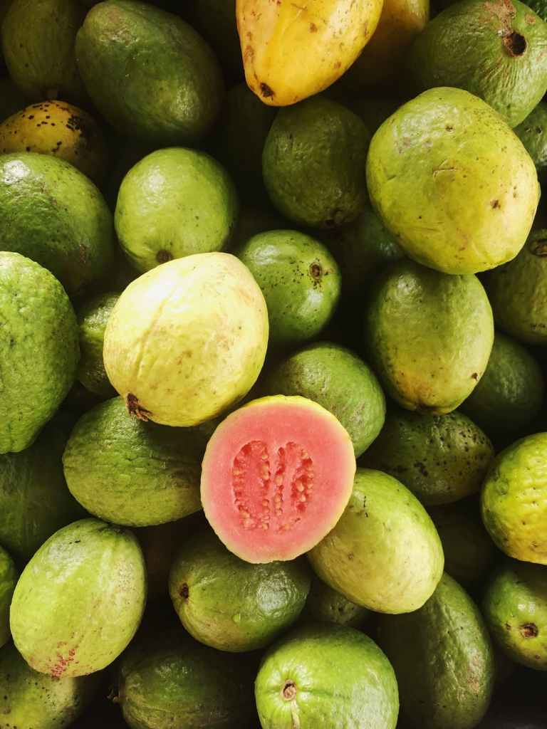 CLOSE UP OF MANY GUAVA, GREEN PEELS, WITH BRIGHT PINK FLESH