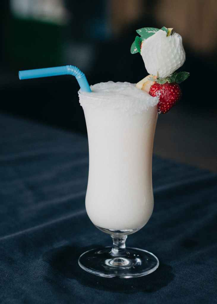 white frozen pina colada in a hurricane glass with a blue bendy straw and garnishes on the lip of the glass. Set against a dark background