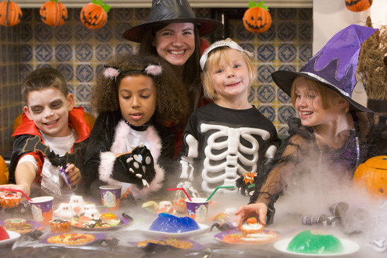 Four young friends and a woman at Halloween eating treats and sm
