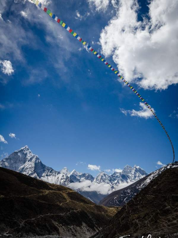 A long prayer flag reaches to the mountains in the Himalayas, Nepal