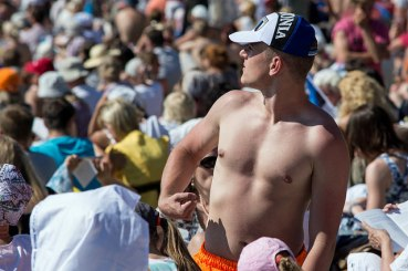 young man flexing his muscles in the crowd