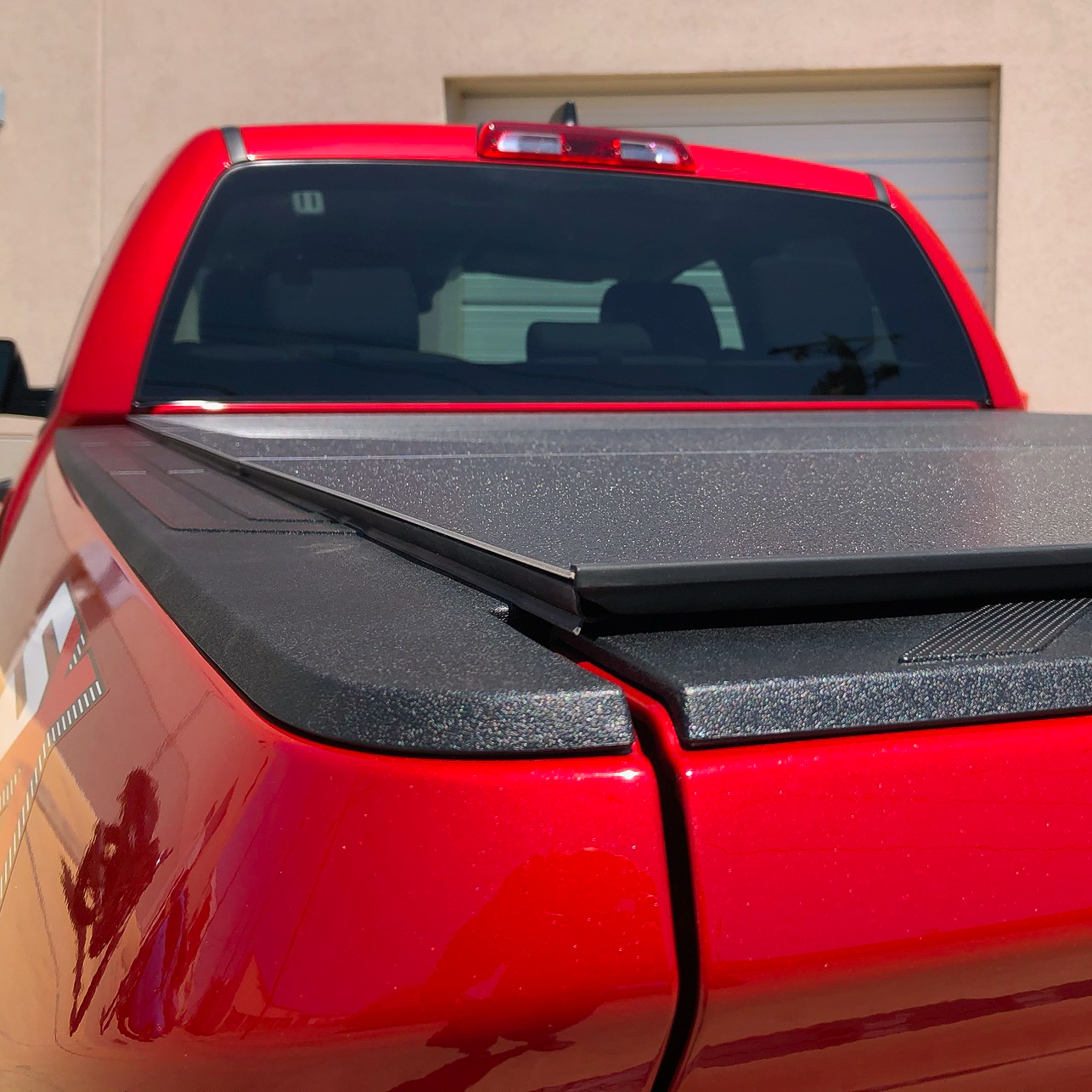 Close-up of covered bed on red truck