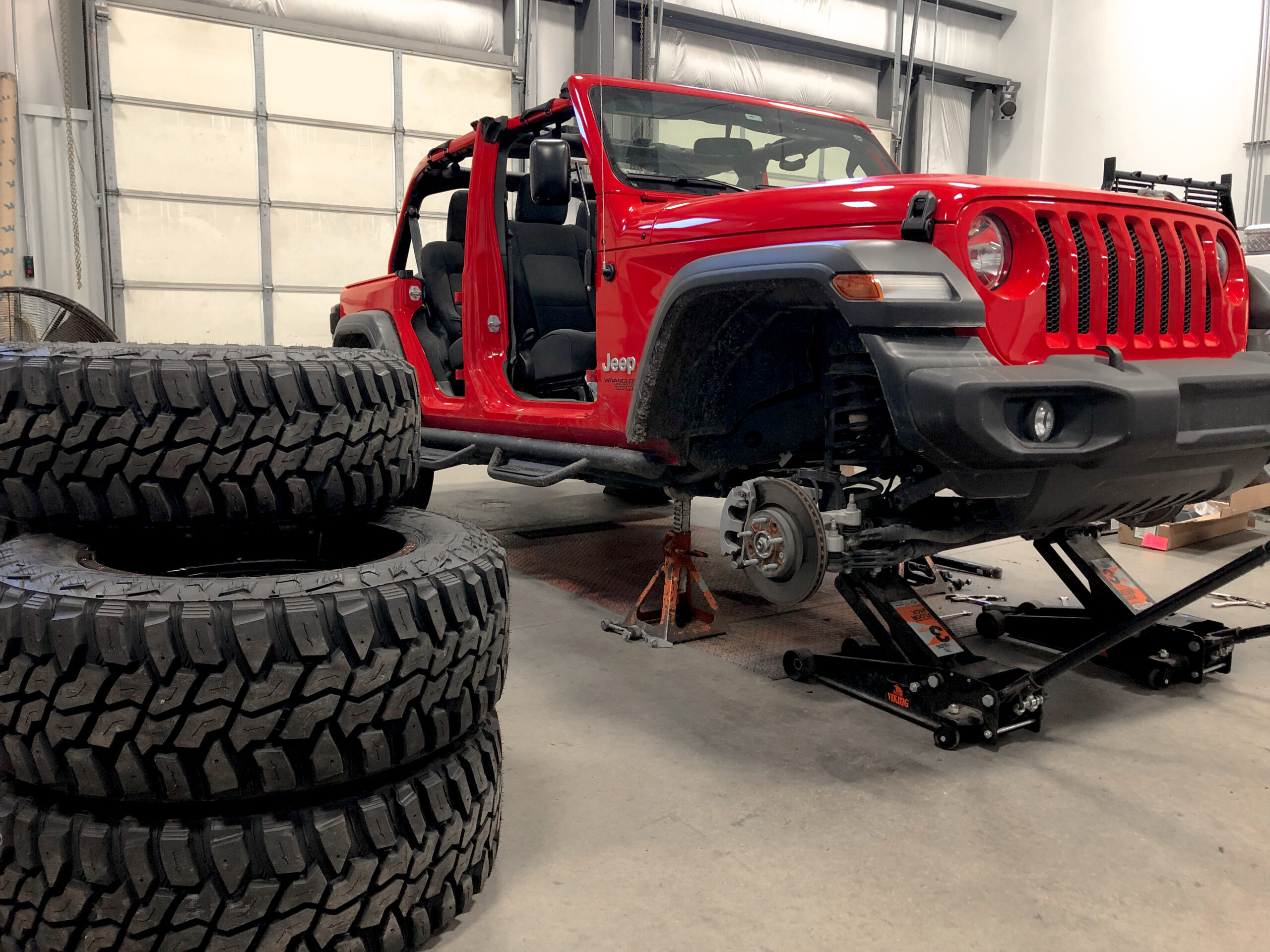 Red Jeep inside shop, resting on a jack and missing a tire