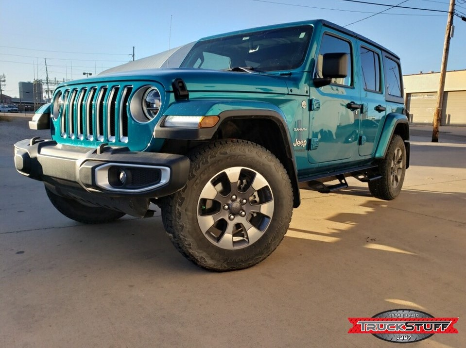 Blue Jeep parked at an angle on concrete pavement outside