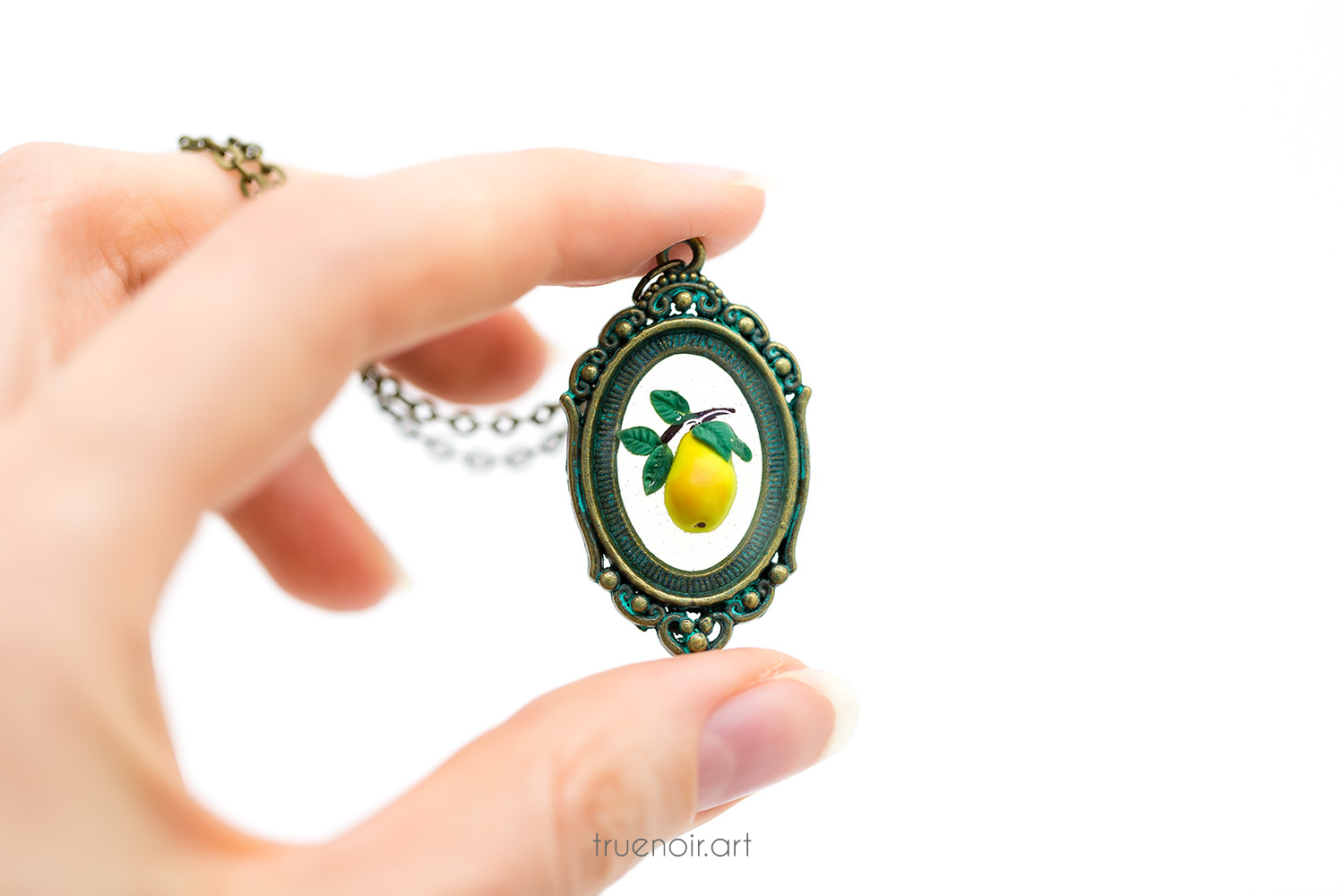 Floating pear pendant held in hand.