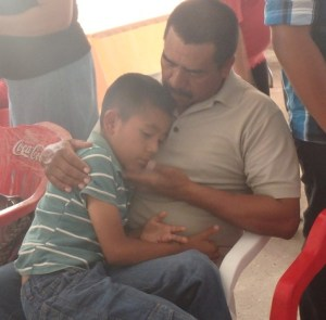 This boy honored his father by simply sitting in his lap during the Hernandez church service.