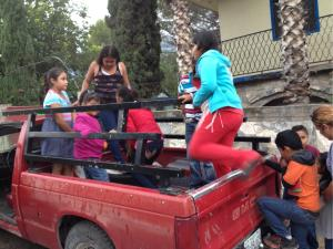 Martin loads the kids from Reynaldo's church in the back of his truck.