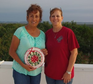 Belinda Bookman and Tonyia pose with a hand made tortilla holder Belinda bought. She and husband Larry donated several items.