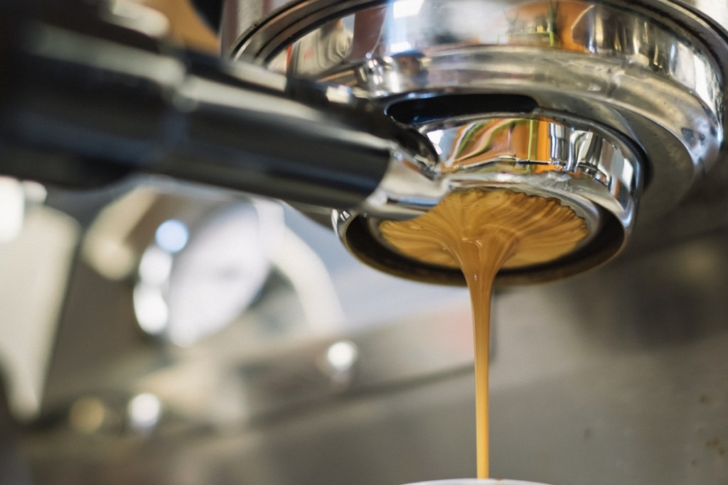 A picture of a shot of caffeine anhydrous flowing from an espresso portafilter.