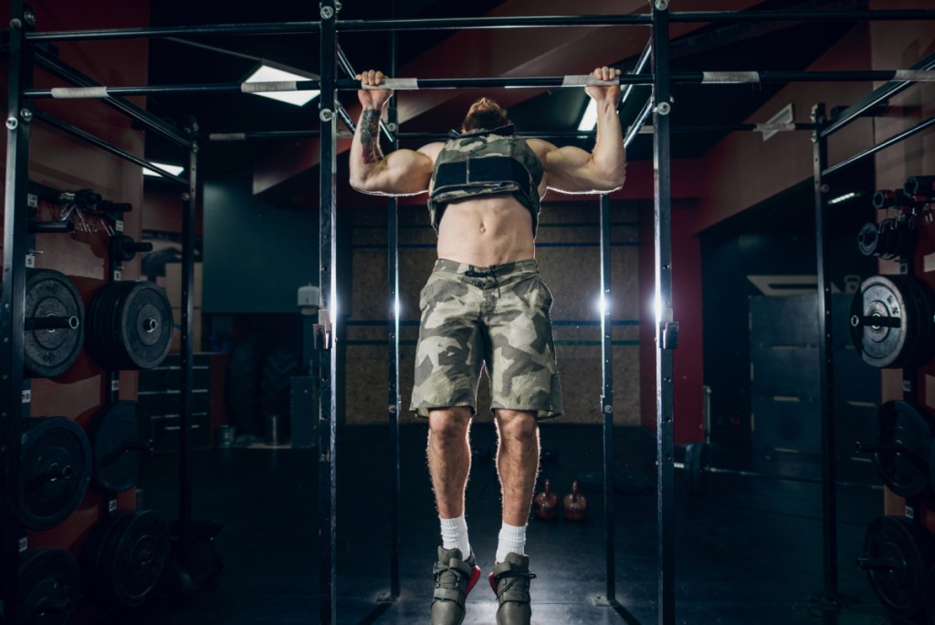 Muscular caucasian bearded man doing pull-ups in military style weighted vest in crossfit gym. Weight plates, kettlebells, barbell and crossfit tires in background.