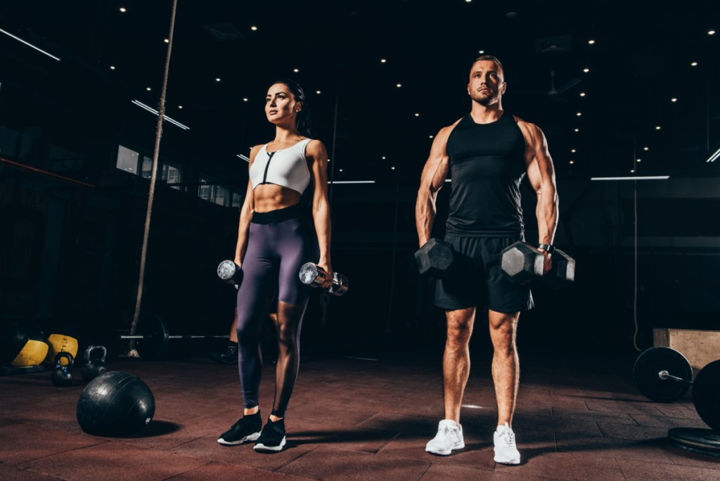 A young couple working out at the gym questioning how long does it take to build muscle.
