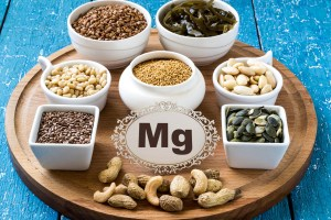 Collection products containing magnesium (buckwheat, cashews, peanuts, pine nuts, almonds, flax seeds and pumpkin, mustard, seaweed) which are all ingredients that also raise testosterone and your libido. on a round cutting board and a blue wooden background