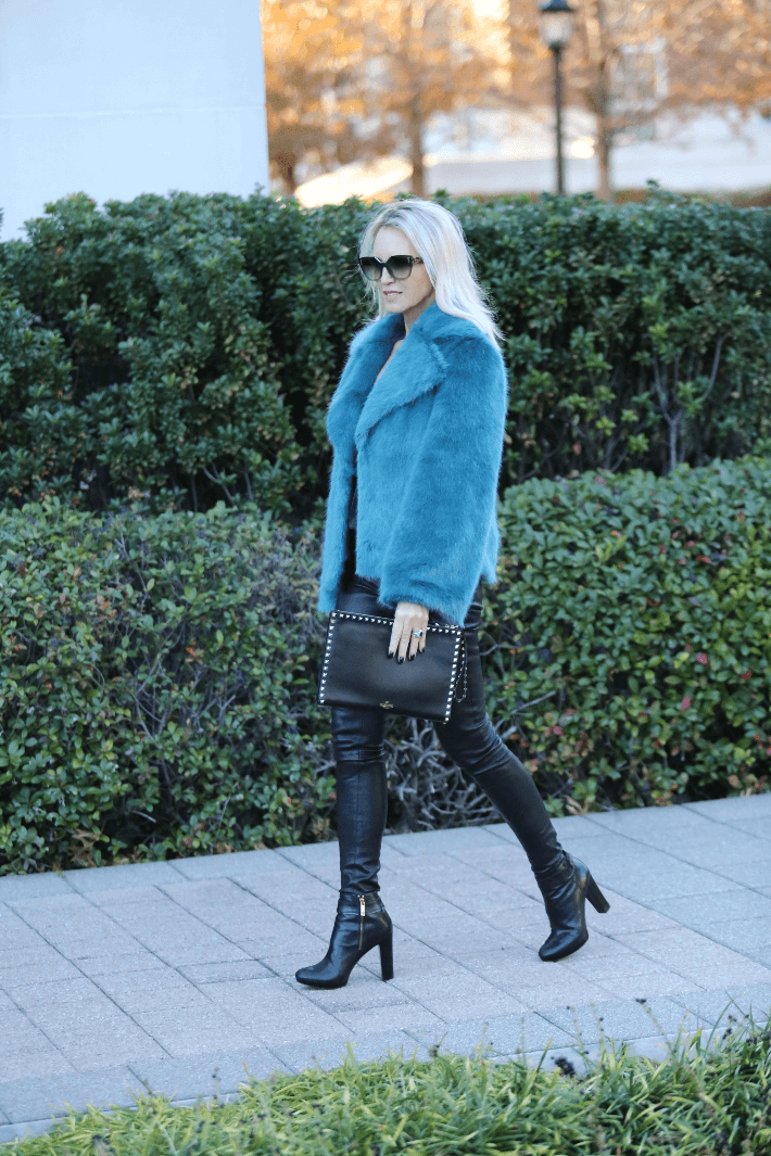 Dallas style blogger 'Truly Megan' wearing blue faux fur jacket, leather leggings and carrying black Valentino Rock Stud Clutch.