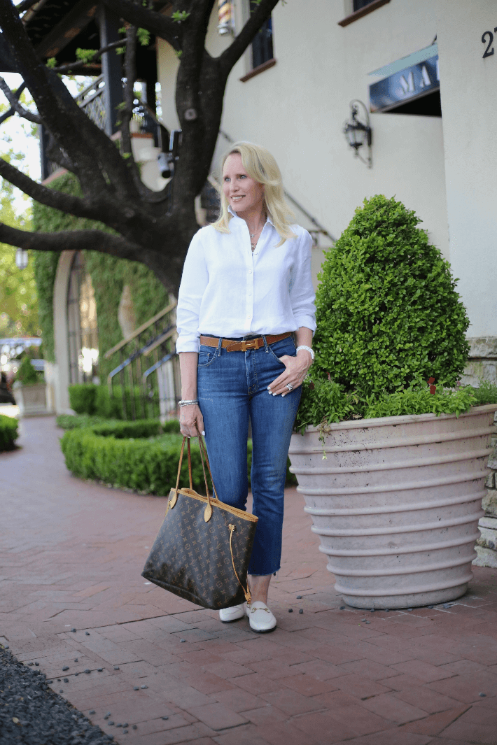 Dallas style blogger Megan Saustad wearing white linen blouse, Hermes belt, Gucci loafers and carrying Louis Vuitton neverfull.
