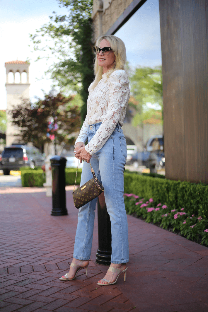 Style blogger wearing white lace blouse, Frame jeans and carrying Louis Vuitton Eva monogram clutch.