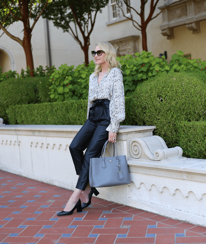 Style blogger wearing black leather paper bag waist pants, snake print blouse and carrying grey Prada handbag.