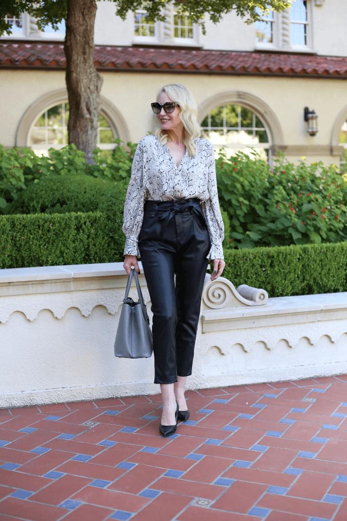 Fashion blogger Truly Megan wearing black faux leather paper bag waist pants, snake print faux wrap body suit and carrying grey Prada handbag.