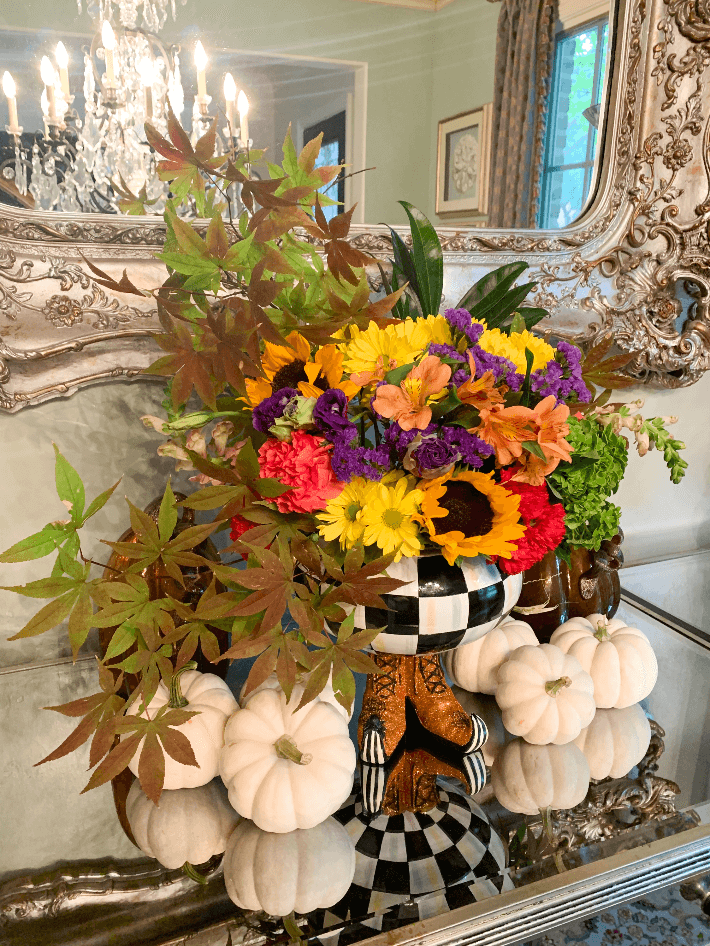 The Mackenzie Childs Halloween Courtly Checked Cauldron on display filled with fresh fall flowers.