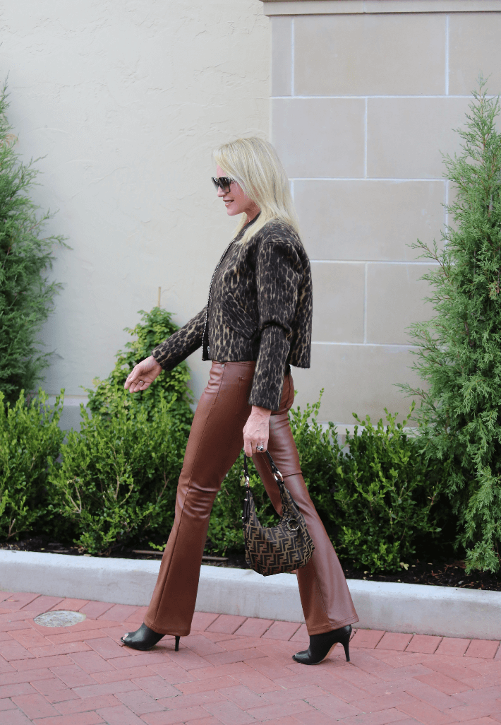 Style blogger wearing camel faux leather pants and leopard bomber jacket.