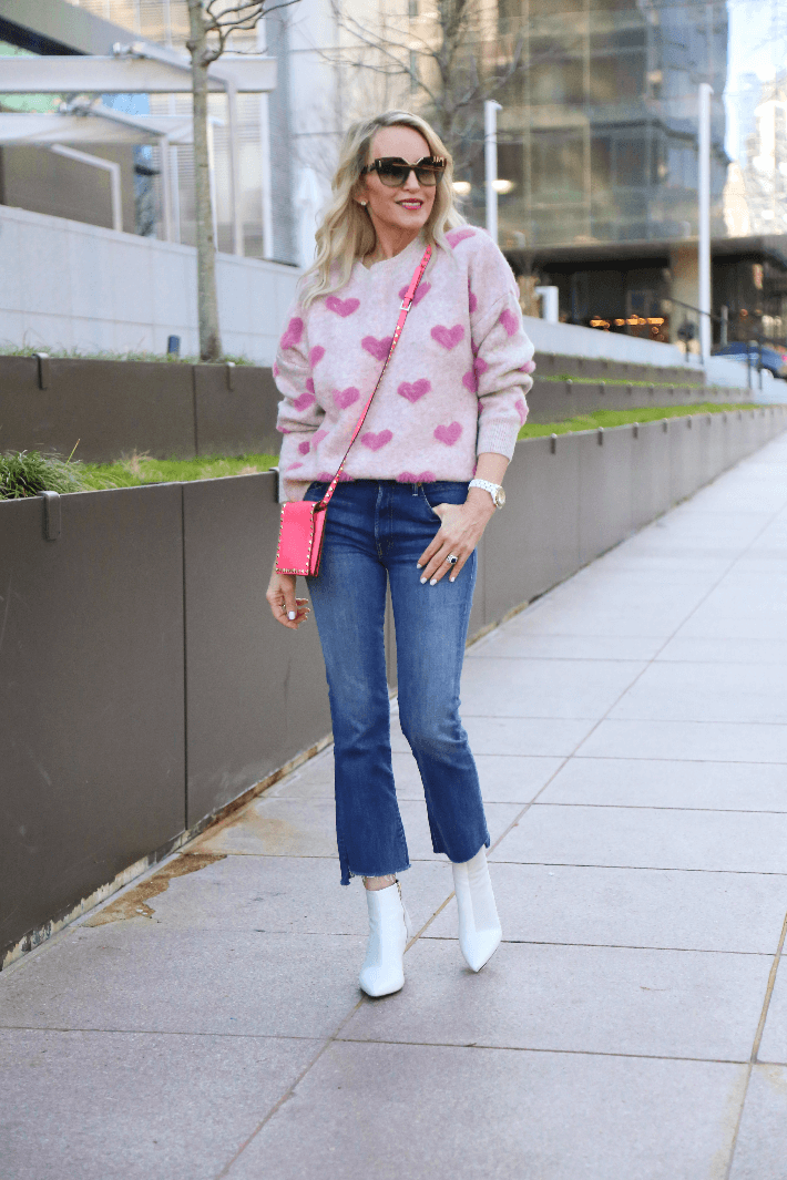Dallas fashion blogger wearing Chicwish pink fuzzy heart sweater, mother step fray jeans, Rag & Bone Beha bootie and carrying Valentino bright pink crossbody bag.