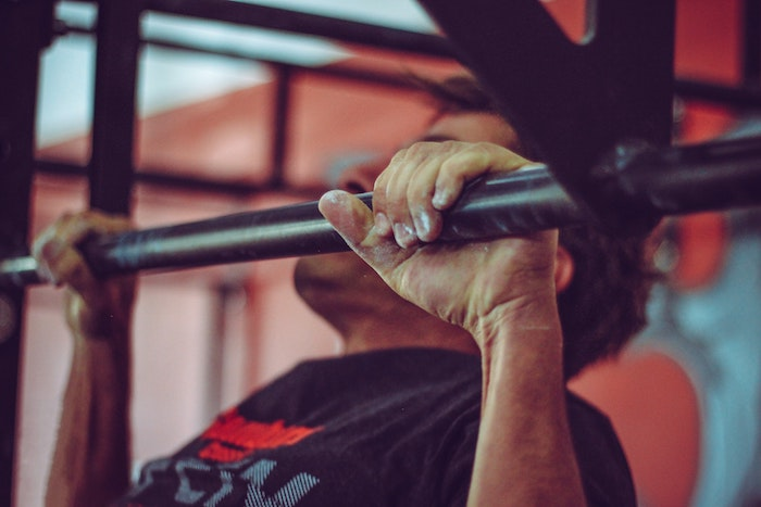 Man doing pull ups at the gym with pull up bar