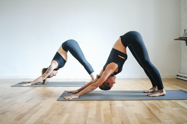 Women in a yoga class doing downward facing dog