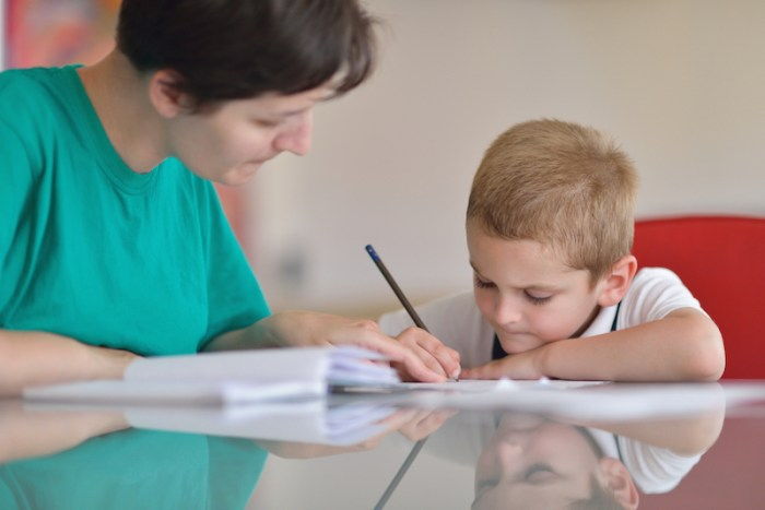 Woman helping boy with homework at a table