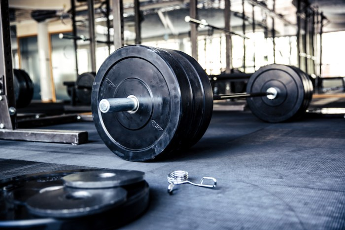 Barbell and bumper plates on gym floor